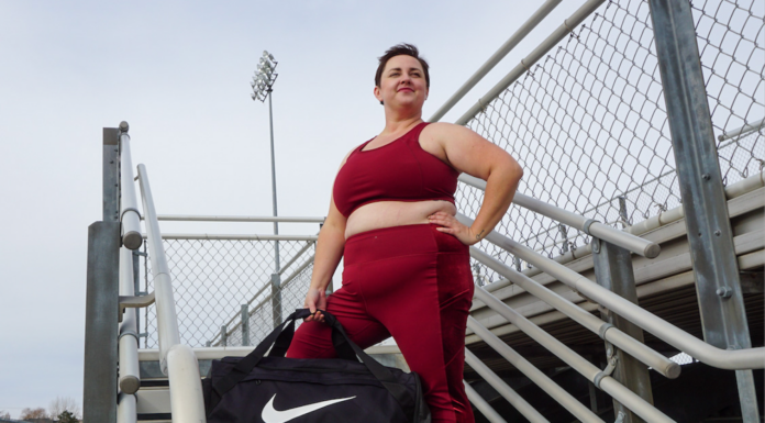 brianne wearing a matching maroon workout set from torrid with a nike bag on a bleacher