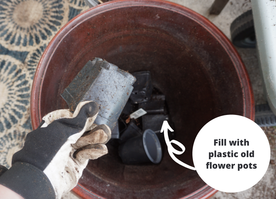 Packing bottom of large pot with material for drainage