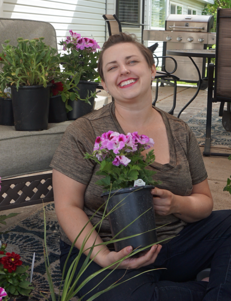 Blogger posing with flowers for container gardening - home improvement project