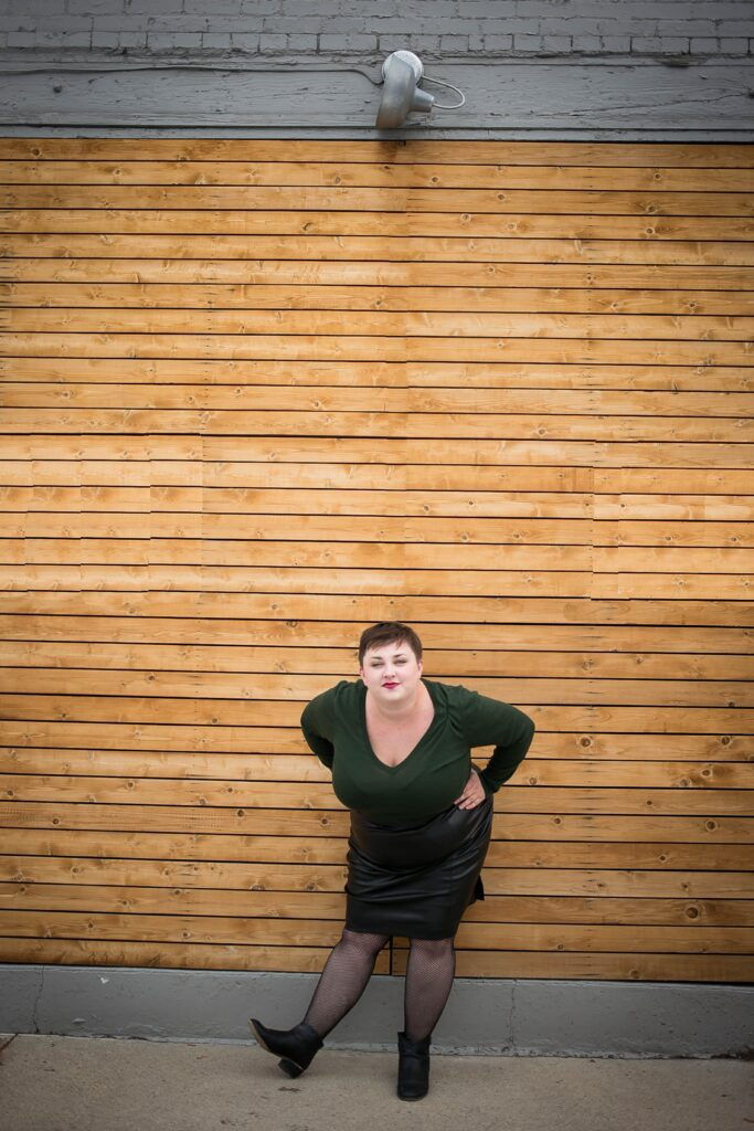 Sassy and fun plus size blogger styling a plus size leather skirt with a sweater and fishnets
