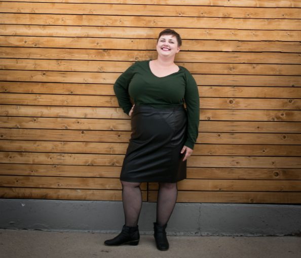 Plus size blogger styling a plus size leather pencil skirt with a sweater and fishnets