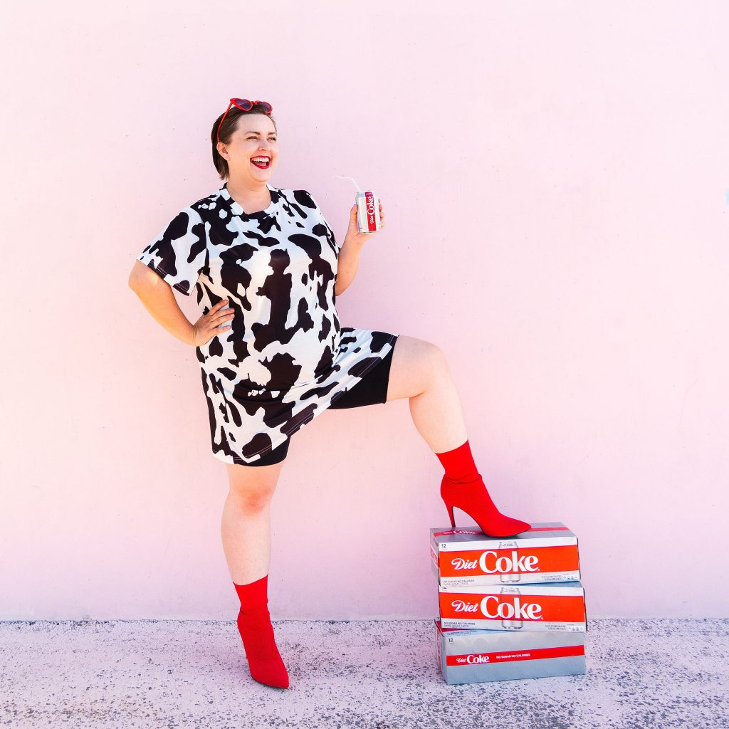 Blogger holding diet coke in cowprint dress laughing in utah