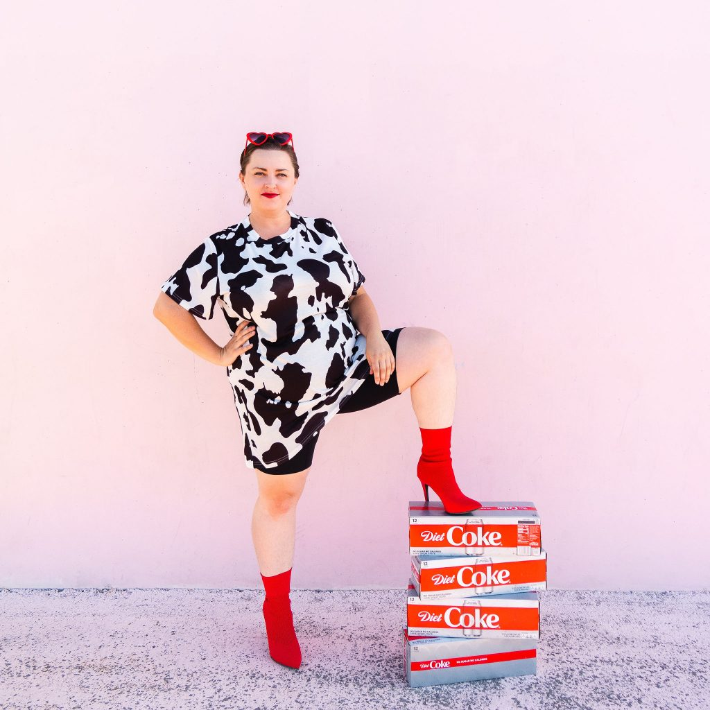 Fashion and lifestyle blogger with diet coke and trendy cow print dress in utah for photoshoot at cents of style
