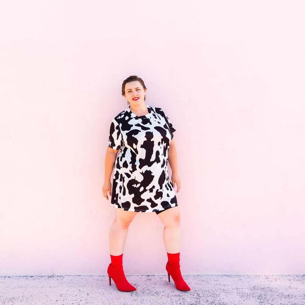 Fashion blogger and model in cowprint dress with red boots