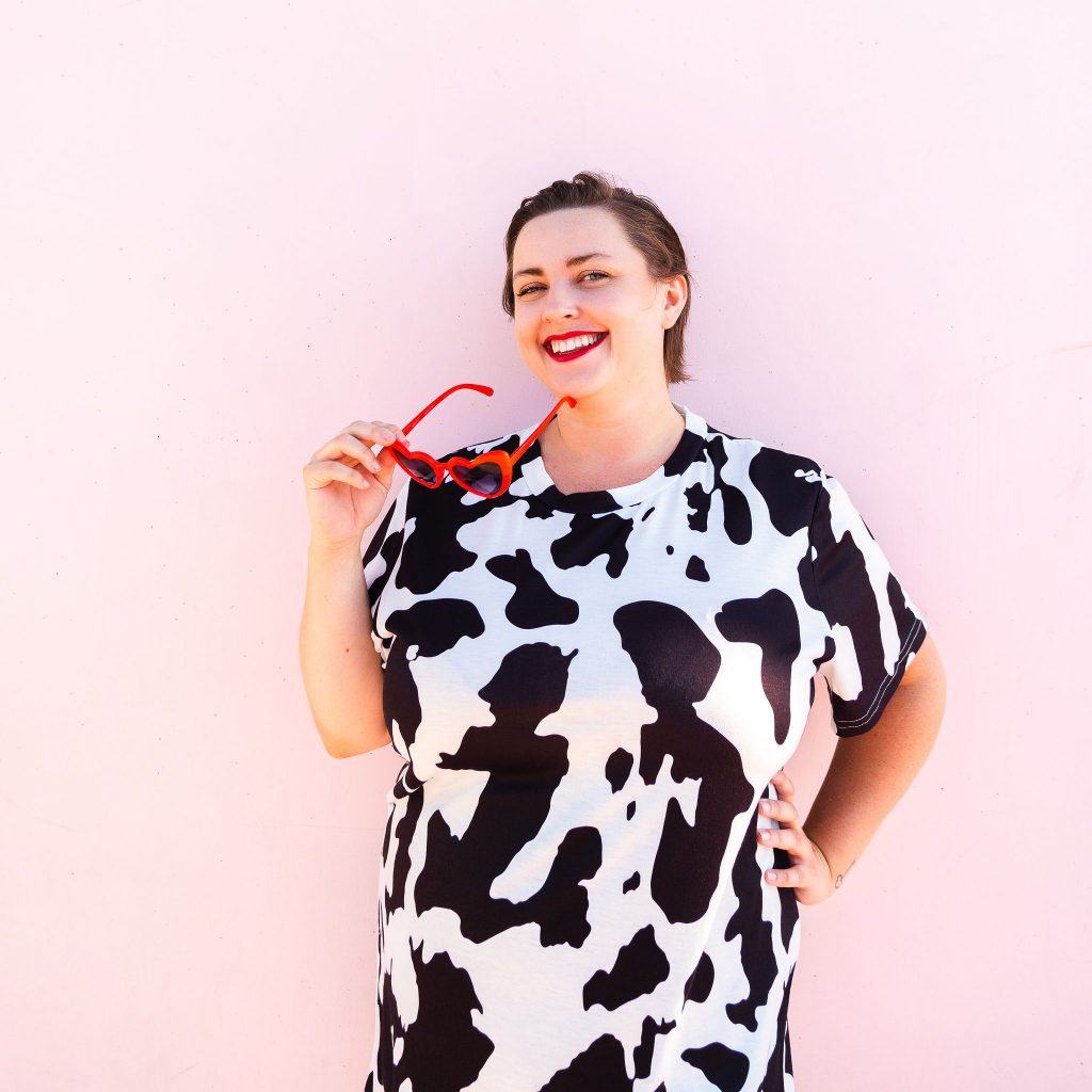 Fashion blogger in cow print t-shirt dress with red boots plus size model
