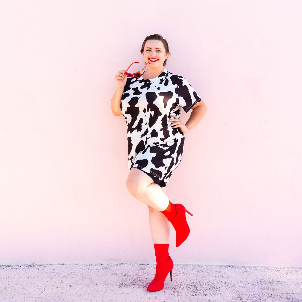 Plus size blogger in cow print fashion dress with red boots in Utah