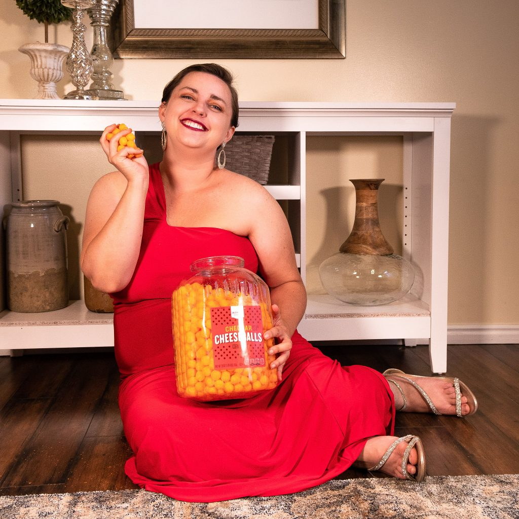 Plus size fashion model in red gown for in-home photoshoot, holding cheese puffs - we love snacks!