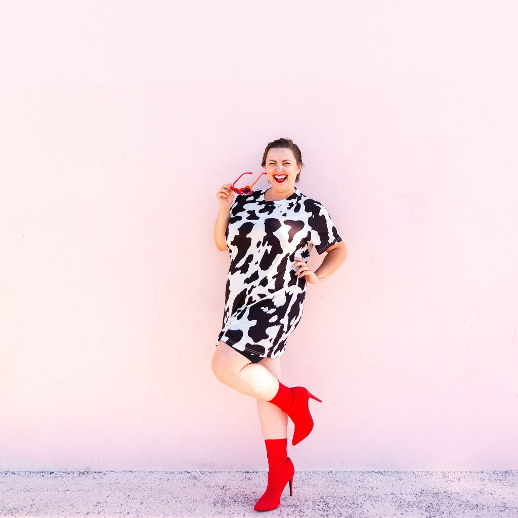 Plus size model in cow print t-shirt dress with red boots in Utah