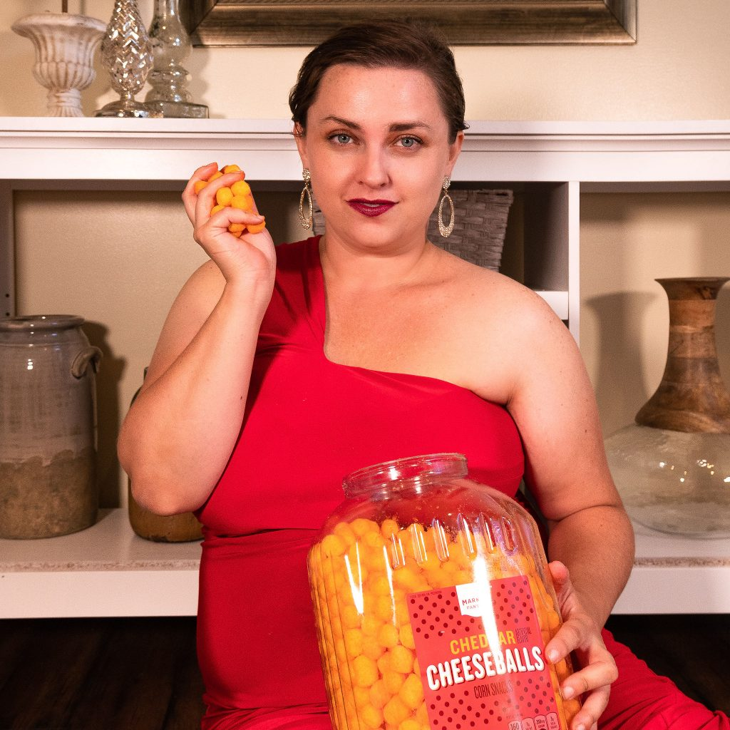 Snack blogger with cheese puffs in fashion photoshoot wearing red floor length evening gown