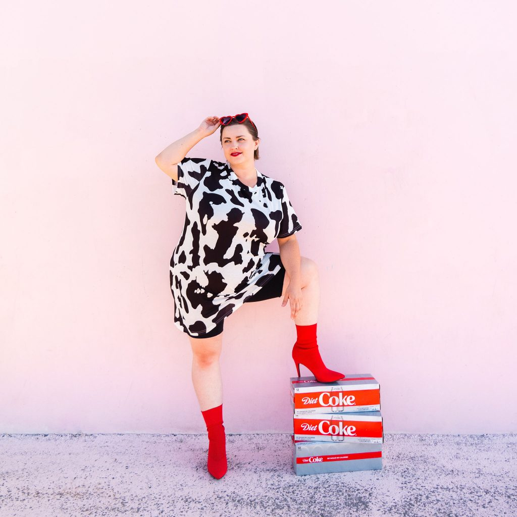 Snack blogger with diet coke and red heart sunglasses in cow print dress with red boots