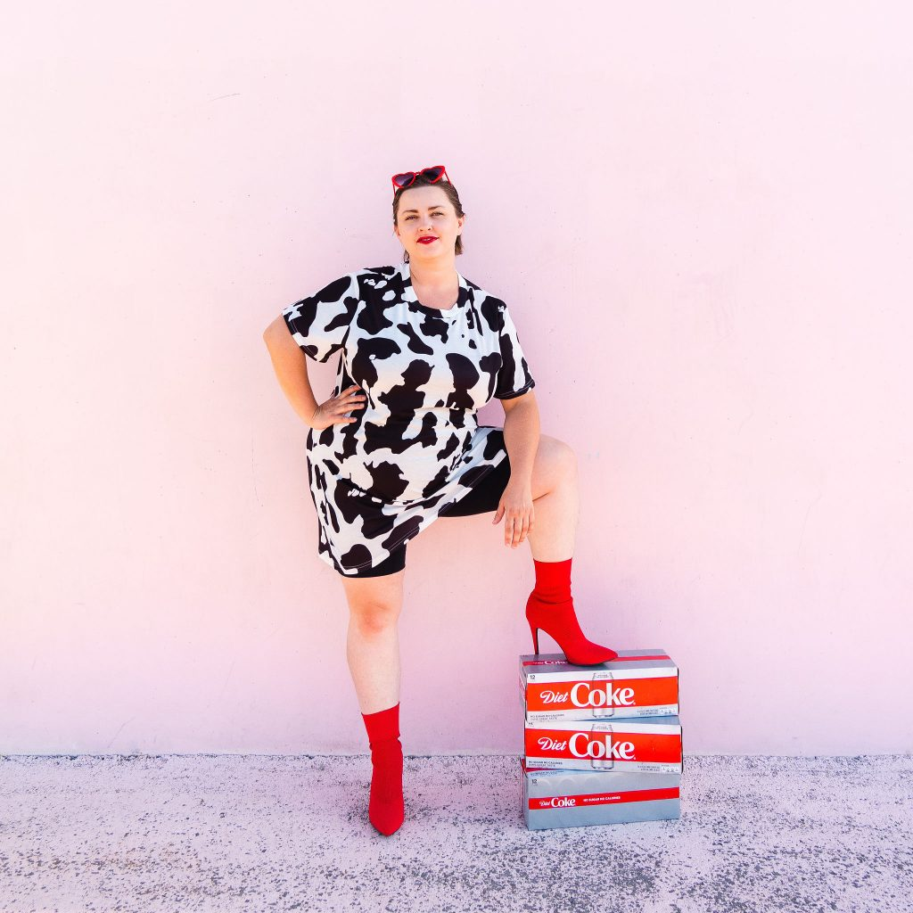 Snack blogger with diet coke and red heart sunglasses in cow print dress with red boots 2