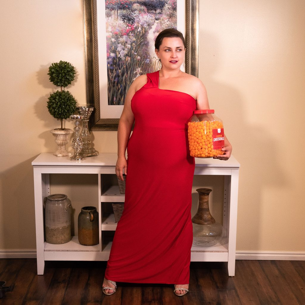 Fashion editorial photoshoot featuring cheese puffs as a snack.  Model in floor length red evening gown.