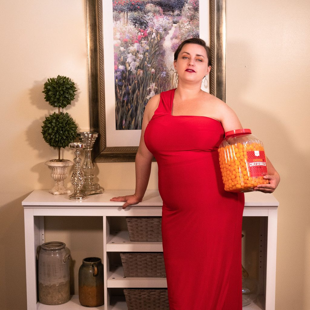 Plus size fashion model from Utah wearing a floor length red gown, holding cheese puffs as a snack for an in-home fashion editorial photoshoot in her living room