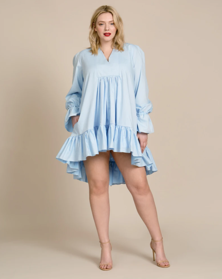 Chicago designer Azeeza Khan is known for feminine and unstructured silhouettes like this one. Crafted from a crisp light blue cotton poplin, the dress has a swingy trapeze cut with a surplice V neckline, blouson sleeves, and a ruffled high-low hem. Fits true to size.