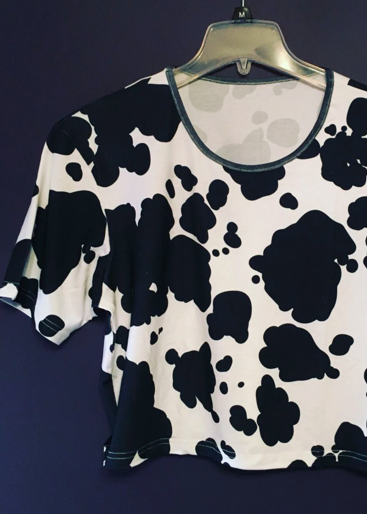 Shopping guide for cow print plus size clothing - image shows a cow print crop top on a hanger