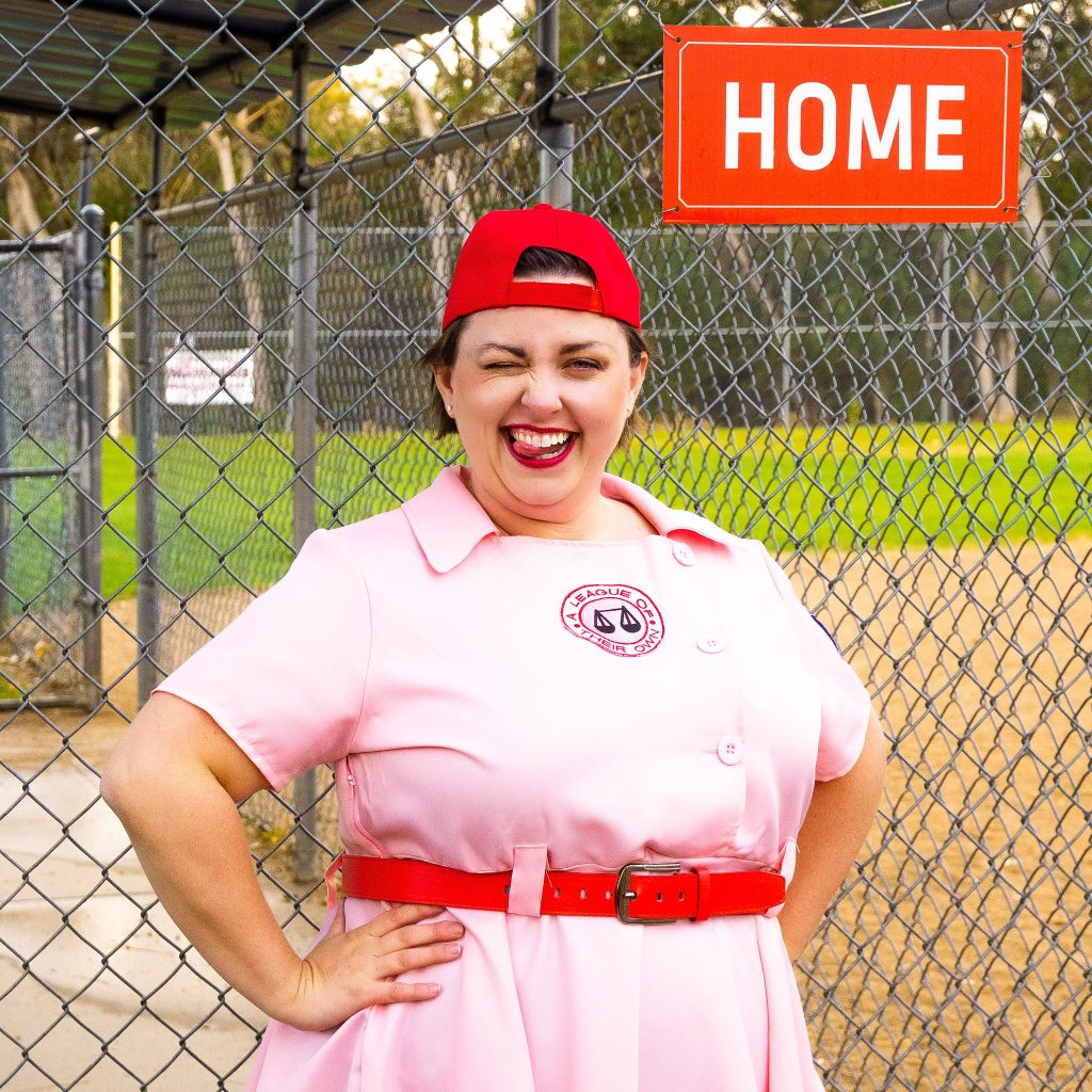 Costume Review - Plus Size a League of Their Own Halloween Costume - pink costume with blogger showing baseball hat on backwards