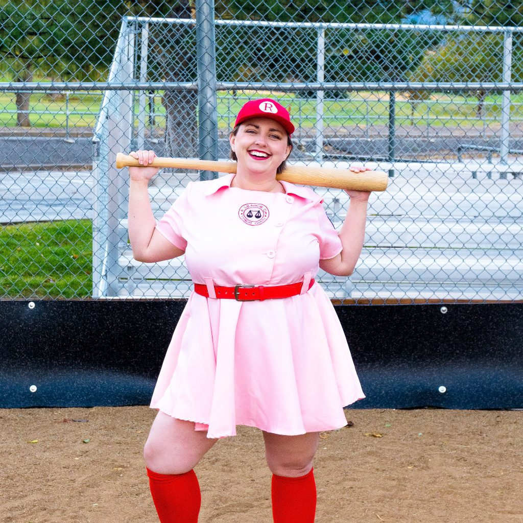 Costume Review - Plus Size a League of Their Own Halloween Costume - pink costume with blogger showing baseball hat on backwards and with baseball bat