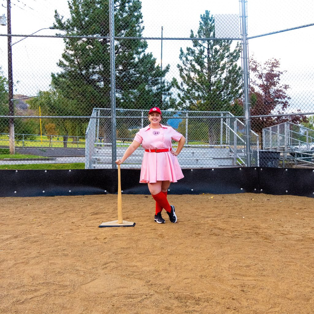 Costume Review - Plus Size a League of Their Own Halloween Costume - pink costume with blogger posing with bat