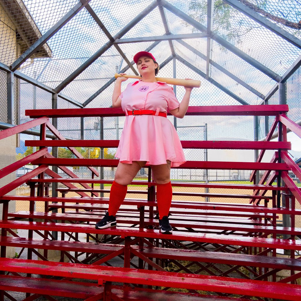 Costume Review - Plus Size a League of Their Own Halloween Costume - pink costume with blogger standing on bleachers