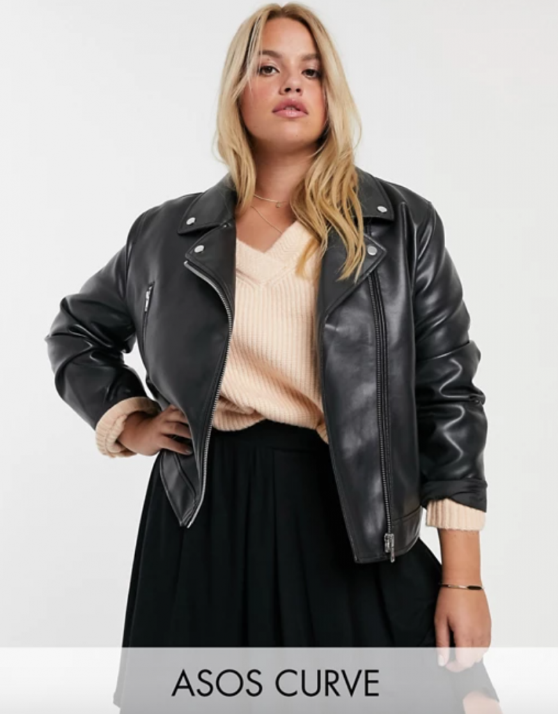 Black plus size moto jacket in faux leather. Blonde model in sweater and skirt and leather jacke