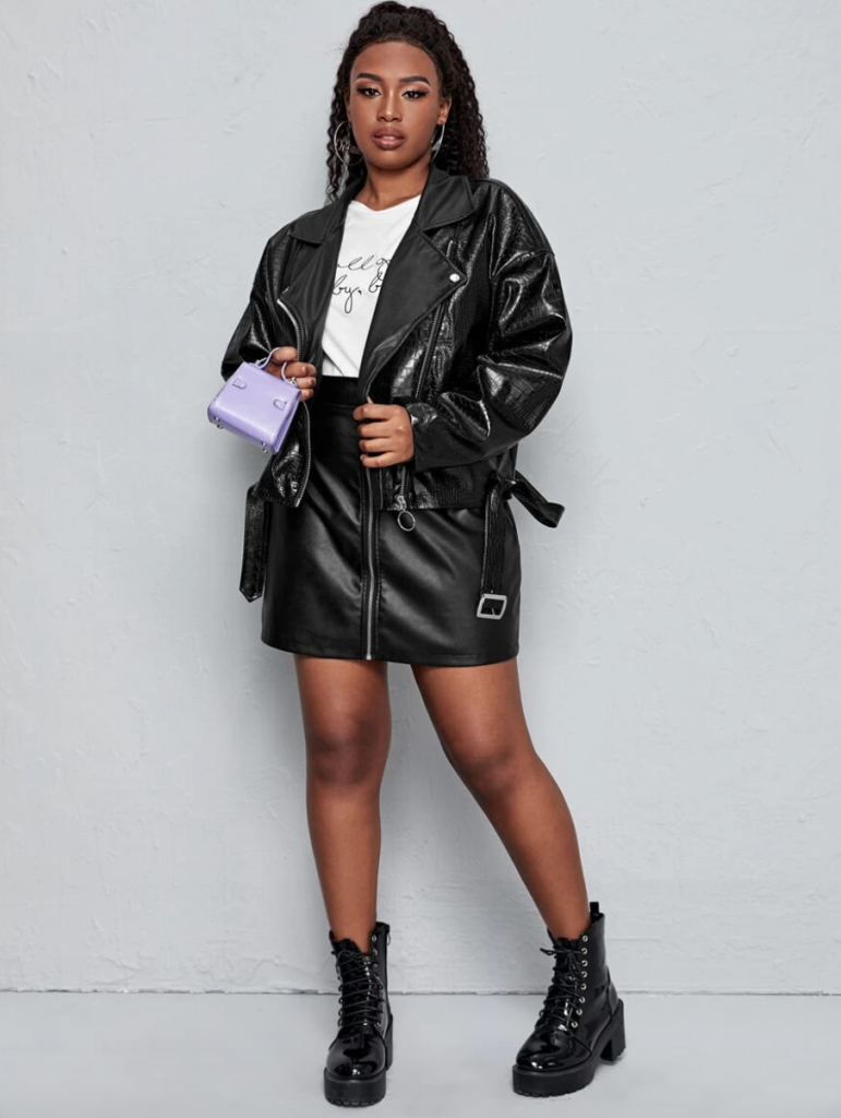 model in black plus size faux leather jacket with faux leather skirt and lavender mini purse