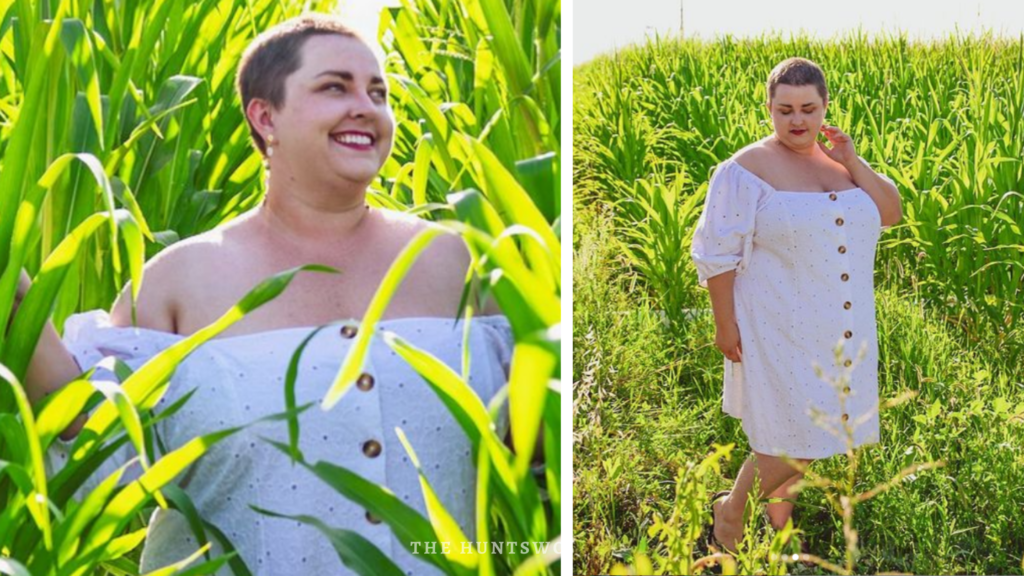 woman with shaved hair and round face with red lipstick in editorial photoshoot in field with white dress