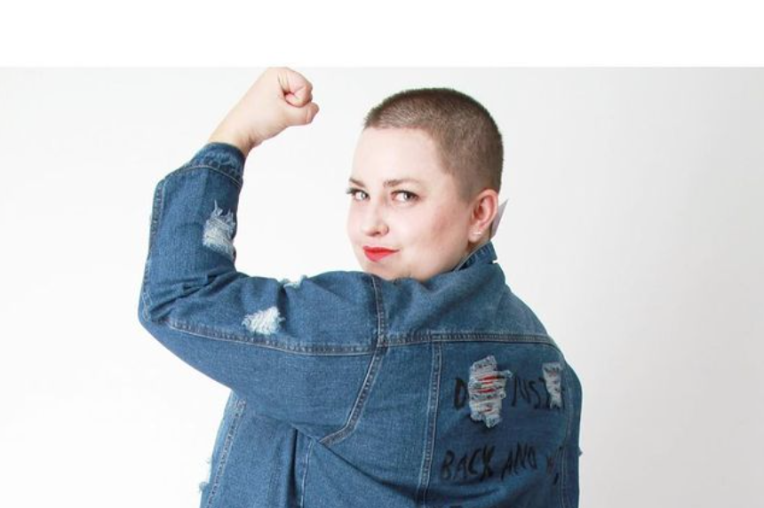 woman with shaved hair and round face with red lipstick in jean jacket