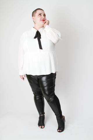 woman with shaved hair and round face with red lipstick in white top and black pants